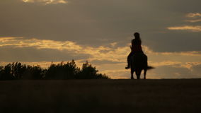 Woman riding horse on field during sunset. Lockdown shot of woman riding horse in nature. Female is enjoying horseback riding on field during sunset. She is with stock video footage