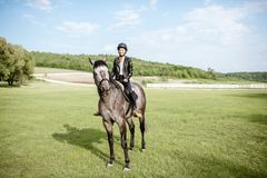 Woman riding horse on the green meadow stock photography