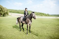 Woman riding horse on the green meadow royalty free stock photo