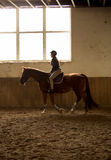 Woman riding horse at indoor manege with big window Stock Images