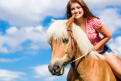 Woman riding on horse in meadow Stock Image