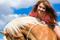 Woman riding on horse in summer meadow Stock Images