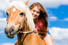Woman riding on horse in summer meadow. Young woman riding on horse in summer meadow Royalty Free Stock Image