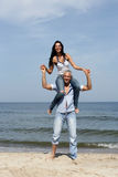 Woman riding on man's shoulders Stock Images