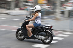 Woman riding a motorcycle. Down an urban street in shorts and summer top with motion blur stock photos
