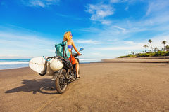 Woman riding a motorcycle with the surfboard stock image