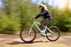 Woman riding a mountain bike on a forest path. Royalty Free Stock Photography