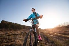 Woman riding mountain bike at sunset Royalty Free Stock Photos