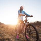 Woman riding mountain bike at sunset Stock Photo