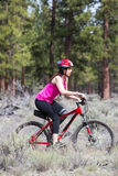Woman riding mountain bike on trail in forest Royalty Free Stock Image
