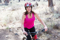 Woman riding mountain bike on trail in forest Stock Photos
