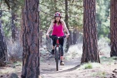 Woman riding mountain bike on trail in forest Stock Images