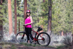 Woman riding mountain bike on trail in forest Royalty Free Stock Photo