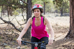 Woman riding mountain bike on trail in forest Stock Photography