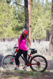 Woman riding mountain bike on trail in forest Royalty Free Stock Images