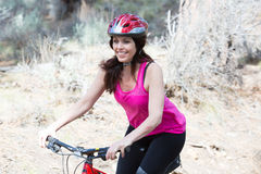 Woman riding mountain bike on trail in forest Stock Photo