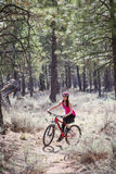 Woman riding mountain bike on trail in forest Royalty Free Stock Photography