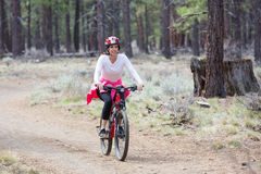 Woman riding mountain bike on trail in forest Stock Image
