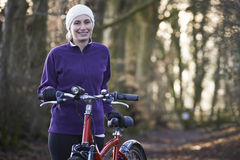 Woman Riding Mountain Bike Through Woodlands Stock Images