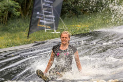 Woman riding muddy water slide. stock images