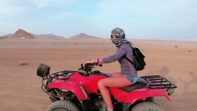 Woman is Riding a Quad Bike in the Desert of Egypt. Dynamic view in motion. stock video footage