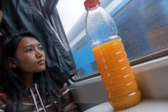 Woman riding by railway with orange juice on table stock photography
