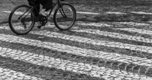 A woman is riding in the rain on a bicycle over the pedestrian path stock photography