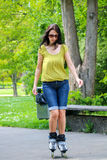 Woman riding on roller skates in park Stock Photography