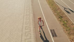 Woman riding a scooter outdoors in summer. Aerial shooting stock video footage