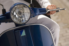 Woman riding on scooter in street, front view, close-up, focus on headlight Stock Photo