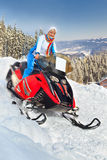 Woman riding a snowmobile. Smiling young woman riding a snowmobile against winter landscape Royalty Free Stock Photo