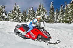 Woman riding a snowmobile. Smiling young woman riding a snowmobile against winter landscape Stock Images