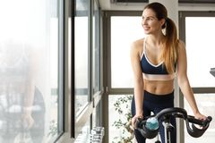Woman riding on stationary bicycle. Happy, sporty woman riding on stationary bike Stock Photo