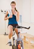 Woman riding stationary bicycle in health club Stock Photography