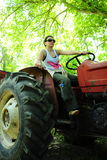 Woman riding tractor Stock Photo