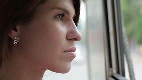 Woman riding in a trolley and looking in window. Woman riding in a trolleybus and looking in window stock footage