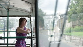Woman riding in a trolley and looking in window. Woman riding in a trolleybus and looking in window stock video