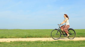 Woman riding a vintage bike on a spring morning stock video
