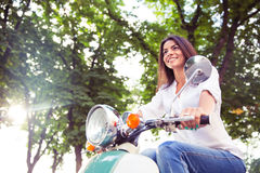 Woman riding vintage scooter Royalty Free Stock Image