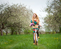 Woman riding vintage white bicycle with flowers basket Royalty Free Stock Photo