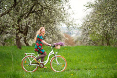 Woman riding vintage white bicycle with flowers basket Stock Photography