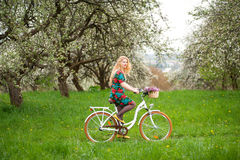 Woman riding vintage white bicycle with flowers basket Royalty Free Stock Photos