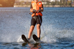 Woman riding water skis closeup. Body parts without a face. Athlete water skiing and having fun. Living a healthy Royalty Free Stock Image