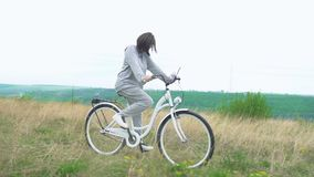 Woman riding white retro bicycle countryside alone.  stock video