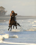 Woman riding wild horse on beach. Woman in formal dress riding wild horse on beach Royalty Free Stock Photo