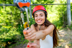 Woman riding on a zip line. Young and pretty woman in red helmet enjoying riding a zip line in the forest. Active summer sports recareation royalty free stock photo