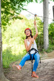 Woman riding on a zip line. Young and pretty woman in red helmet riding on a zip line in the forest. Active sports kind of recreation royalty free stock photos