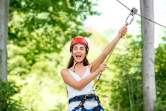 Woman riding on a zip line. Young and pretty woman in red helmet riding on a zip line in the forest. Active sports kind of recreation royalty free stock photo
