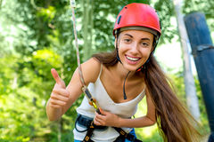 Woman riding on a zip line. Young and pretty woman in red helmet riding on a zip line in the forest. Active sports kind of recreation royalty free stock photography
