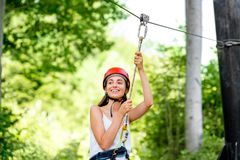 Woman riding on a zip line stock image